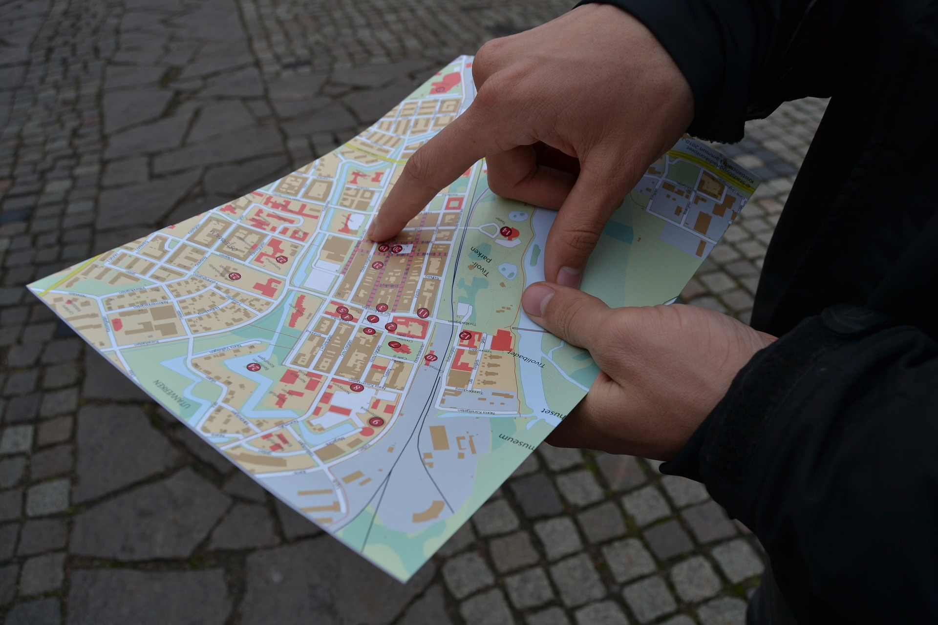 Hands holding a map, finger pointing to destination